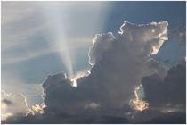 Ein letzter Sonnenstrahl bricht durch Gewitterwolke